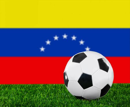 The Venezuelan flag and soccer ball on the green grass. photo