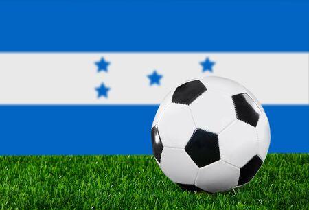 The Honduran flag and soccer ball on the green grass. photo
