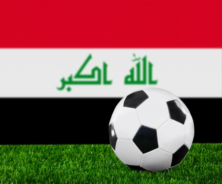 iraqi: The Iraqi flag and soccer ball on the green grass.