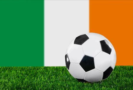 The irish flag and soccer ball on the green grass. photo