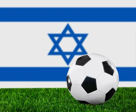 The Israeli flag and soccer ball on the green grass. photo