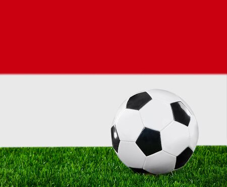 The Indonesian flag and soccer ball on the green grass. photo