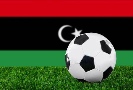 libysch: Die libysche Flagge und Fu�ball auf dem gr�nen Rasen. Lizenzfreie Bilder