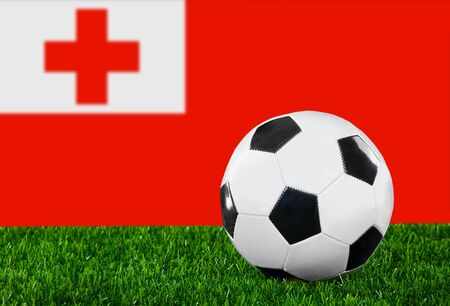 The Tonga flag and soccer ball on the green grass.