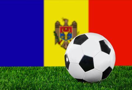 moldovan: The Moldovan flag and soccer ball on the green grass.