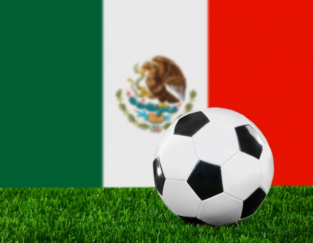 The Mexican flag and soccer ball on the green grass. photo