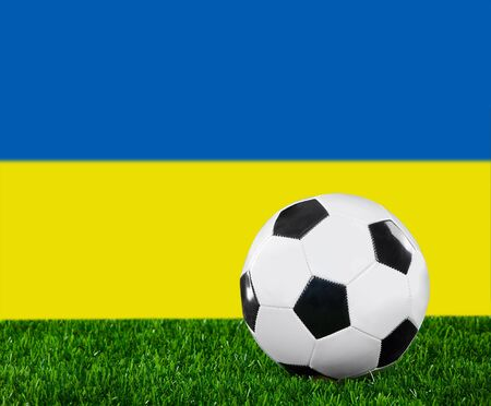 The Ukrainian flag and soccer ball on the green grass. photo