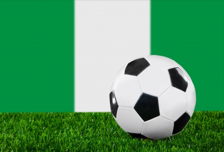 The Nigerian flag and soccer ball on the green grass. photo