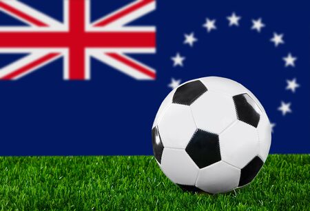The Cook Islands flag and soccer ball on the green grass. photo