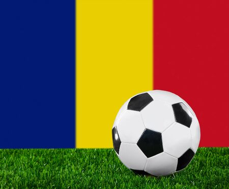 The Romania flag and soccer ball on the green grass. photo