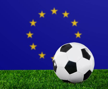 european championship: The European Union Flag and soccer ball on the green grass.