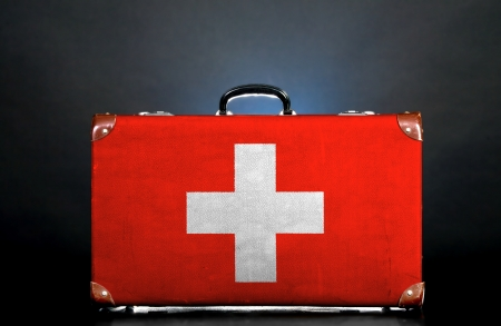 The Swiss flag on a suitcase for travel. photo