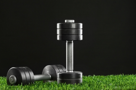 Iron dumbbell on green grass  Фото со стока