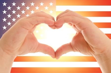 Childrens hands show signs of heart on the background of the American flag