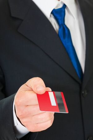Businessman holds out a credit card. Closeup. Stock Photo - 15943769