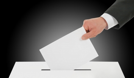 Manhand down ballot in the ballot box. Dark background. photo
