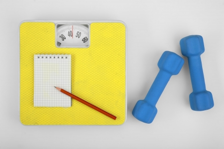 Scales, notebook with pencil and a dumbbell  photo