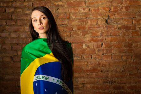 woman in the Brazilian flag on the background of a brick wall photo