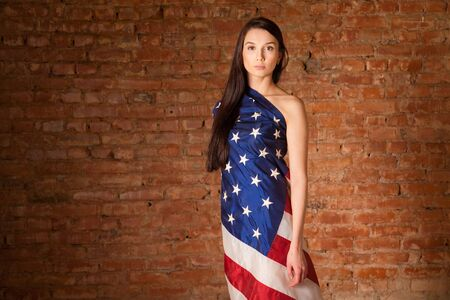woman in the American flag on the background of a brick wall photo