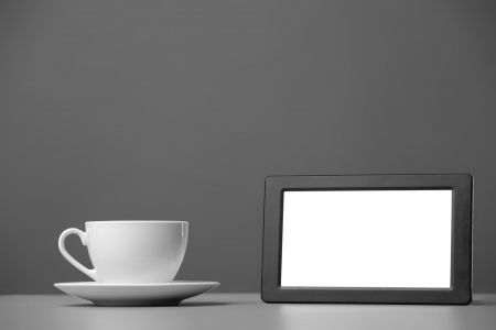 White mug and tablet computer on a gray background  photo