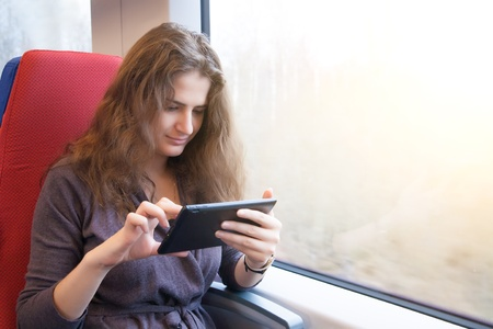 computer user: A woman with a tablet pc on a train ride
