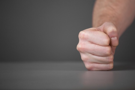 reproach: Male fist on the table  On gray background Stock Photo