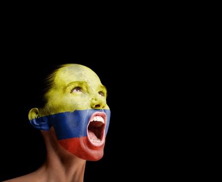 Die kolumbianische Flagge auf dem Gesicht eines schreienden Frau Konzept Standard-Bild