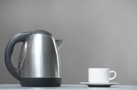 Kitchen kettle and cup on a gray background  Closeup photo