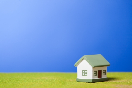 Toy model house on green grass  Conceptual image