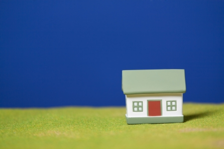 Toy model house on green grass  Conceptual image photo