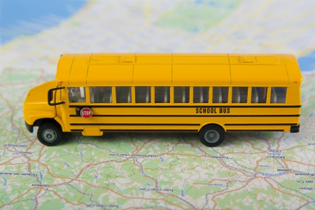 yellow schoolbus: School bus and road map  Closeup, selective focus  Stock Photo