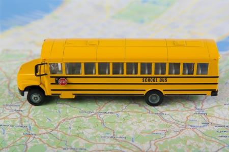 atlas: School bus and road map  Closeup, selective focus  Stock Photo