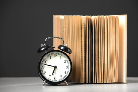 alarm clock with book on black background photo