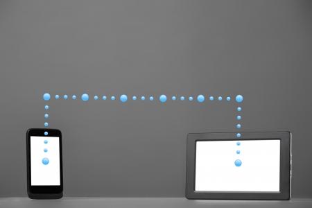 sincronizacion: Smartphone y Tablet PC en un gris concepto de sincronizaci?n de fondo
