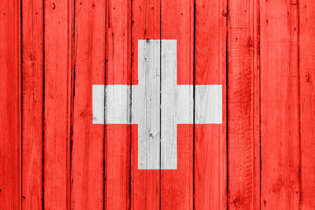 The Swiss flag painted on a wooden fence photo
