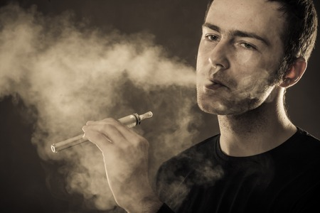 Man smokes electronic cigarette on dark background  Фото со стока