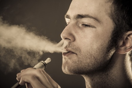 smoker: Man smokes electronic cigarette on dark background  Stock Photo