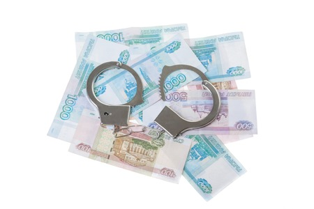 fraudster: financial crime. Steel handcuffs and money, isolated on white