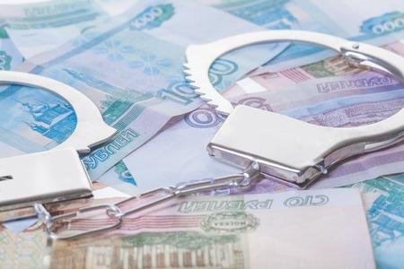 fraudster: financial crime. Steel handcuffs and money, closeup