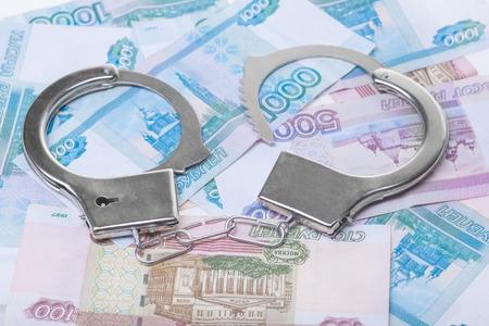 venal: financial crime. Steel handcuffs and money, closeup