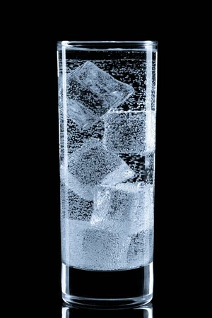 soda water: Glass with soda water and ice cubes. Isolated on black.