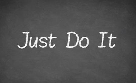 Motivational phrase - just do it, handwritten with white chalk on a blackboard