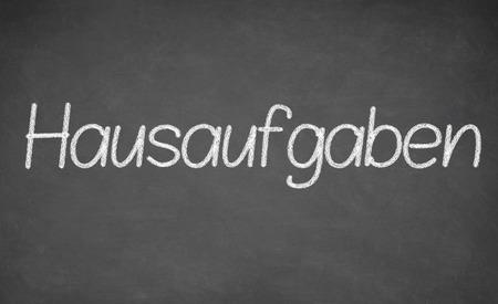 revision: Homework written on chalkboard - in German language - Hausaufgaben Stock Photo