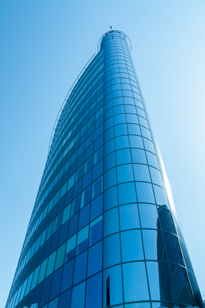 rise to the top: The top of modern high rise building. Blue sky. Toning Stock Photo