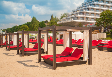 Empty sunbeds in a row on the sand beach and hostel Stock Photo