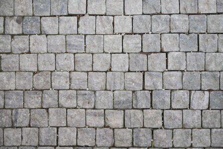 brick floor: Stone pavement texture. Granite cobblestoned pavement background. Abstract background of old cobblestone pavement close-up. Stock Photo