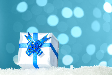Decorative white gift box with blue bow standing in snow against - background bokeh of twinkling party lights Stock Photo