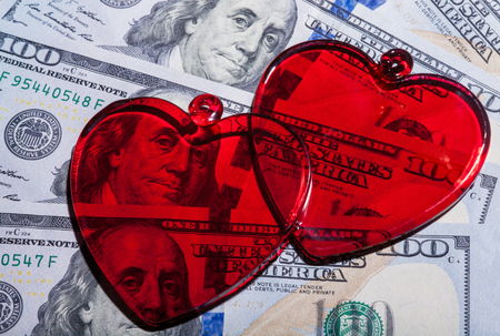 Red glass hearts on dollar bills