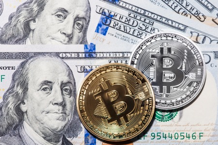 two us dollar: Two Bitcoins on hundred dollars bills.