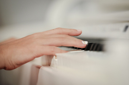 piano closeup: Hand playing on digital piano. Close-up. Small depth of field.